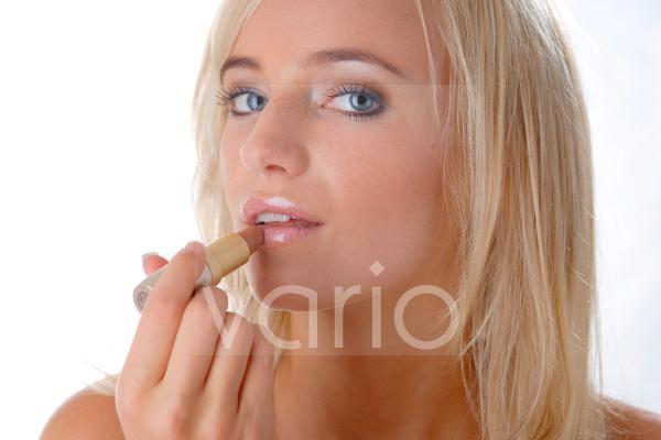 Model beim Auftragen des Lippenstiftes