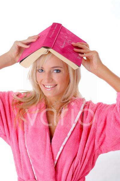 Junge Frau mit einem Buch auf dem Kopf