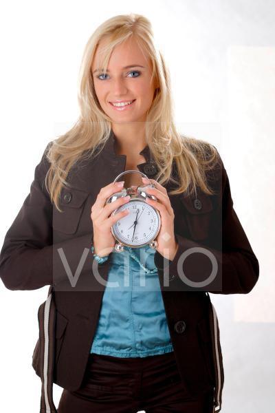 Junge Frau mit einem Wecker in der Hand