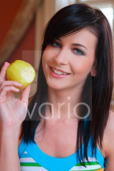 Junge Frau die eine Apfel in Händen hält