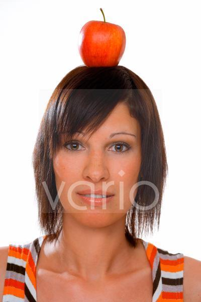 Junge Frau mit einem Apfel auf dem Kopf