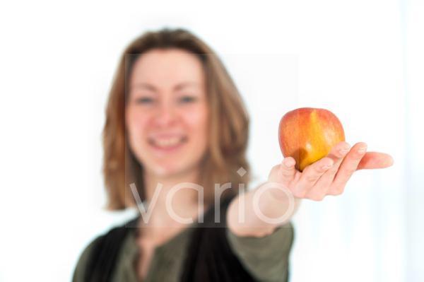 junge Frau hält einen Apfel in der Hand