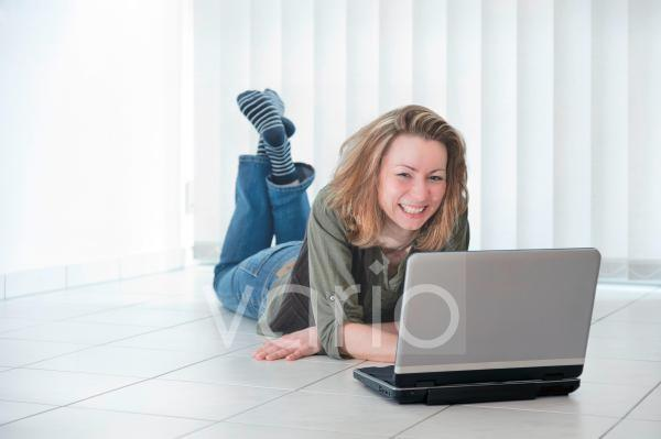 junge frau liegt mit einem Laptop auf dem Fussboden