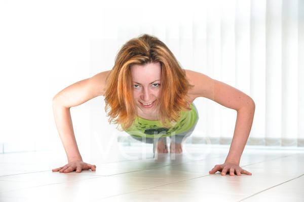 junge Frau macht Liegestütze auf dem Fußboden