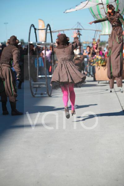 Frau mit rosa Strümpfen im Maskenumzug mit Rhönrad und phantasievollen Kostümen, die an die Flugpioniere erinnern