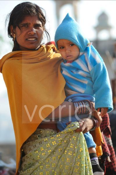 Indian woman carry his son in her hands