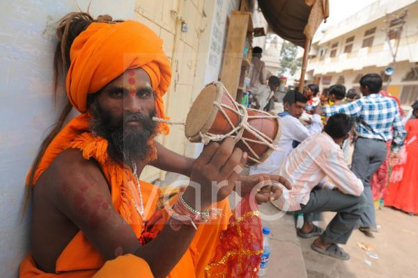 Indian holy man play drum