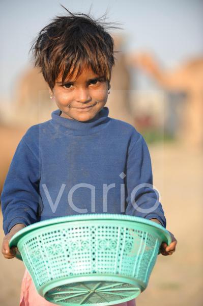 Little indian girl carry basket in the desert