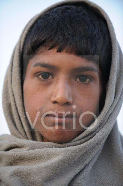 Indian boy wrapped with blanket