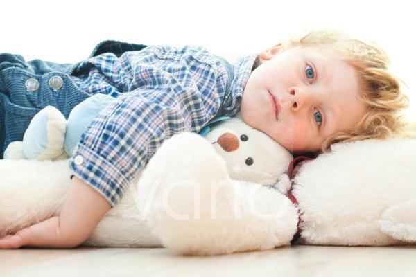 Junge liegt auf seinem Teddybär