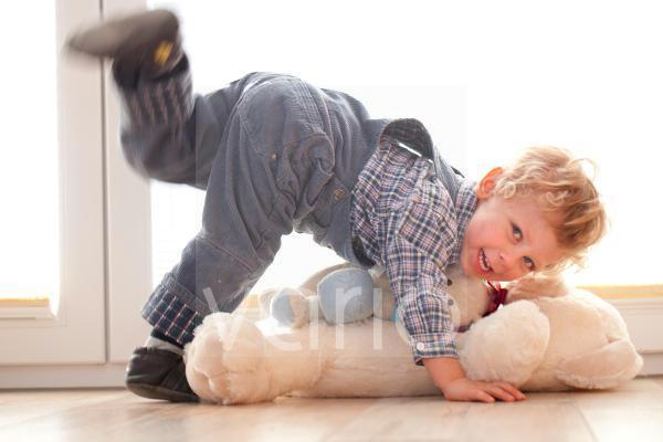 Junge spielt mit seinem Teddybär