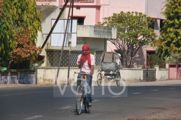 An Indian man wearing a scarf to protect his face from dust and air pollution rides his bicycle along the street
