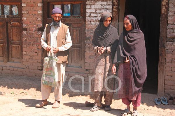A Muslim family outside their rural home in Kashmir