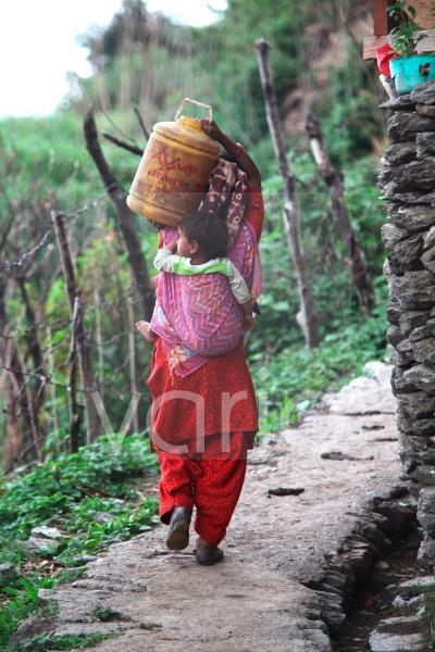 A Hindu Rajput woman carries her child and a jug filled with drinking water