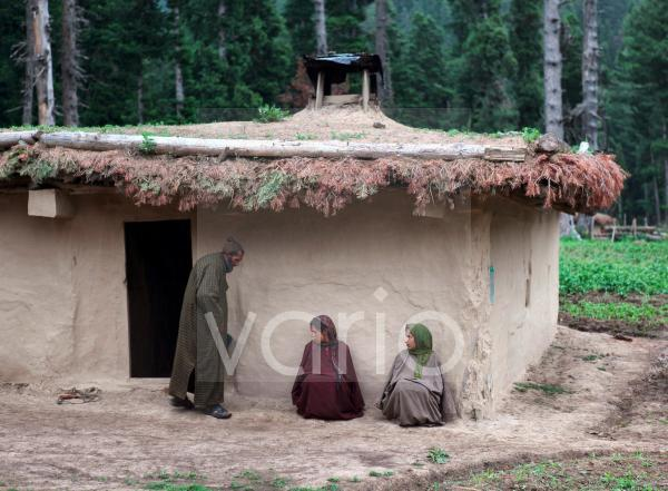 A father talks to his two daughters in front of their traditonal Kashmiri mud house