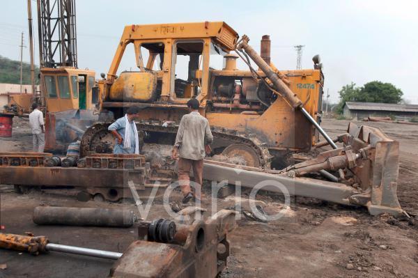 Workers fix heavy machinery at the Gauri Ballarpur Coal Mine