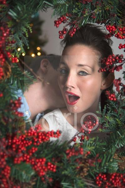 Portrait of young affectionate couple, surrounded by Christmas wreath