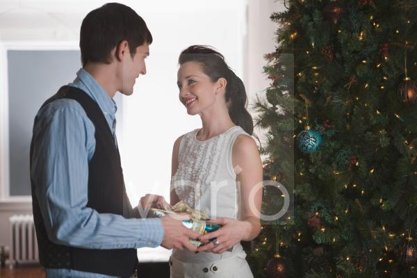 Portrait of young couple exchanging gifts at Christmas