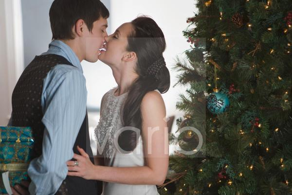Portrait of young couple kissing next to Christmas tree