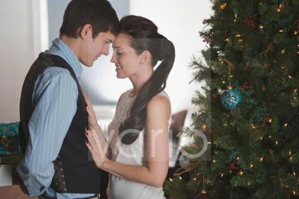Portrait of romantic young couple being affectionate on Christmas