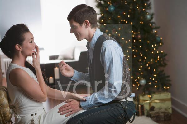 Young man proposing to woman on Christmas