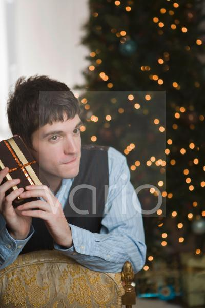 Portrait of young man shaking Christmas gift