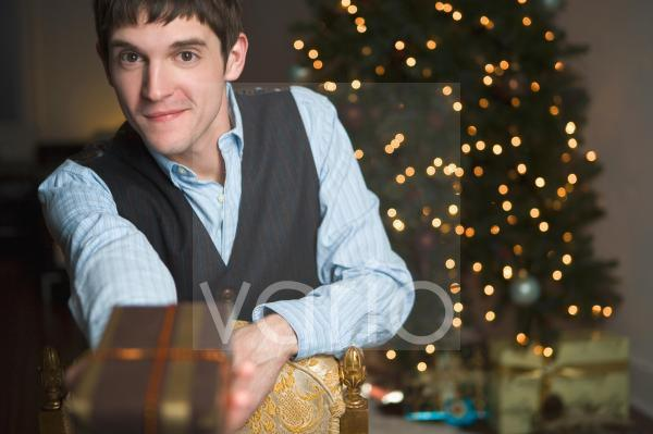 Portrait of young man giving Christmas gift