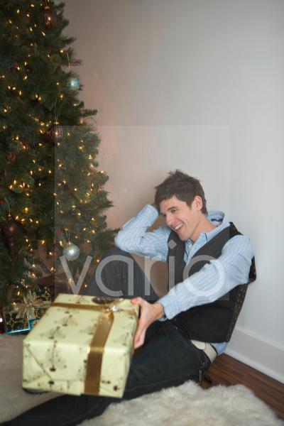 Portrait of smiling young man with gift on Christmas