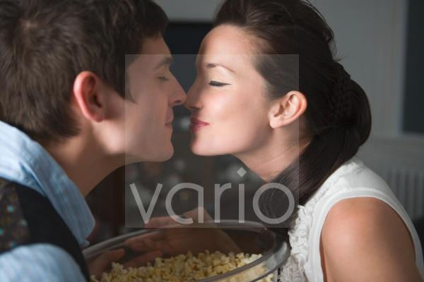 Portrait of young couple kissing at home and eating popcorn