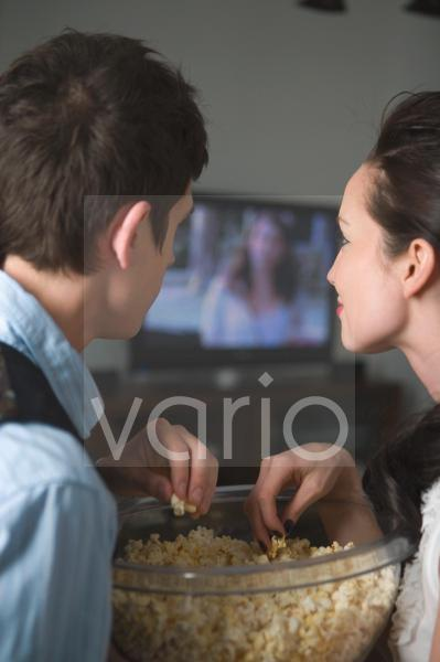 Portrait of young couple watching TV at home and eating popcorn