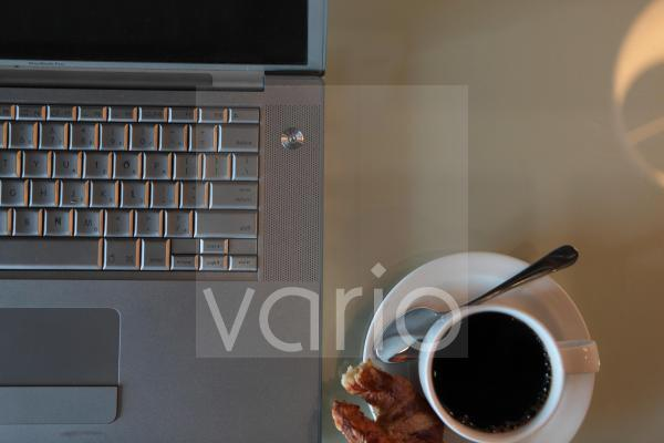 Overhead view of black tea on table by laptop