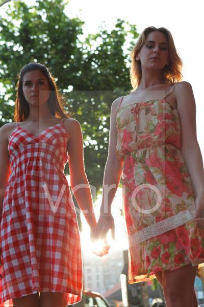 Low angle view of two beautiful young women holding hands