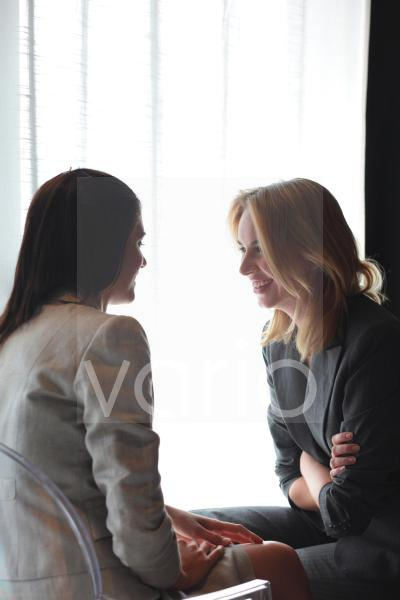 Two cheerful business women looking at each other