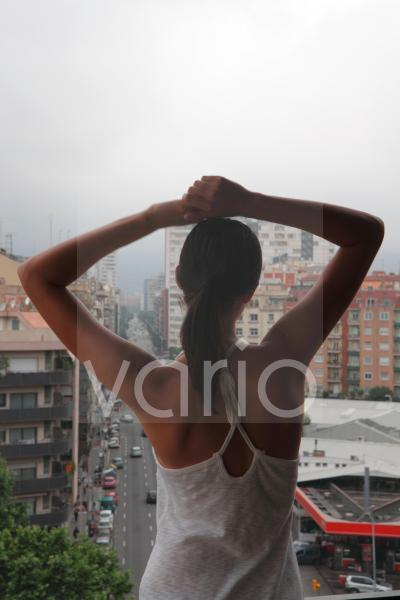 Rear view of woman watching from window with arms outstretched