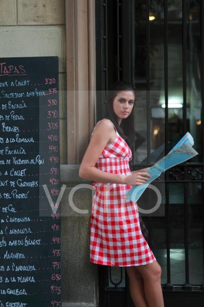 Portrait of young woman standing by menu holding map