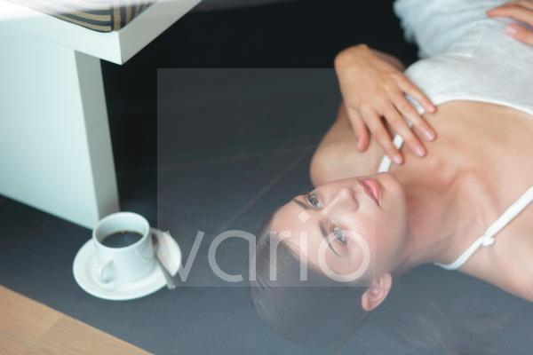 Young woman in contemplation lying on floor by black tea cup