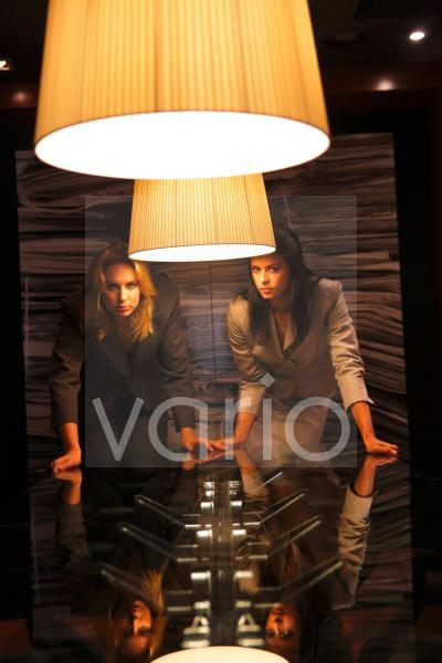 Two young business women staring behind illuminated lamp