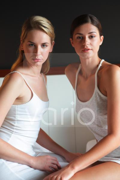 Portrait of two young women sitting side by side