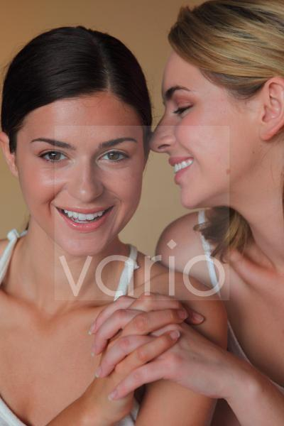 Portrait of two beautiful young women smiling, holding hand