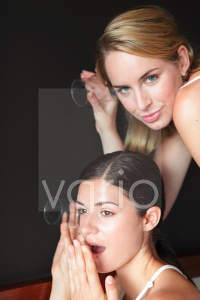 A lesbian couple holding glasses to eavesdrop against wall