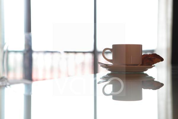 Teacup reflecting on table with spoon