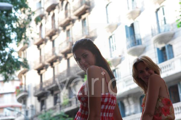 Low angle view of two cheerful young women standing with building in the background