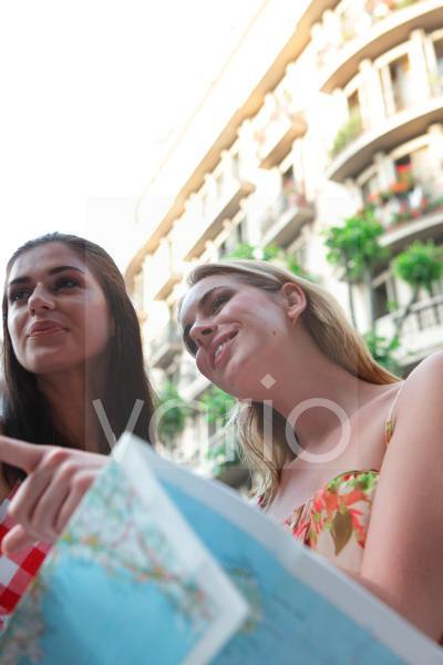 Low angle view of two cheerful young women standing holding map, with building in the background