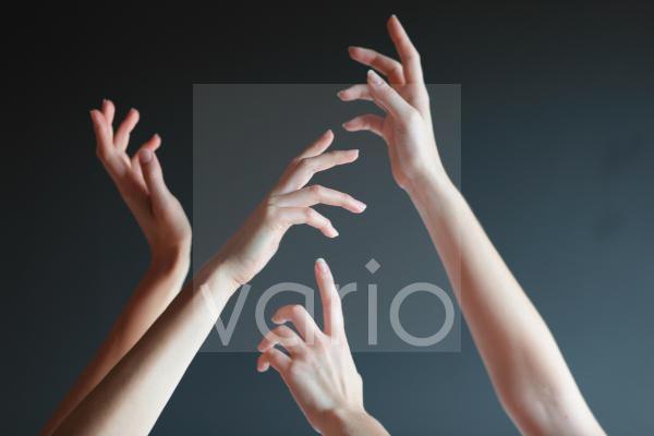Hands of lesbian couple reaching upwards