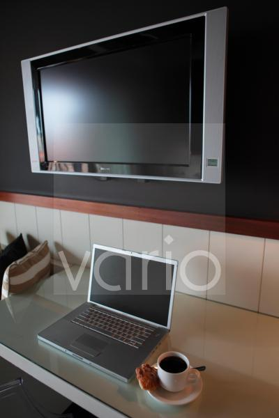 Black tea with laptop on table by flat screen television set