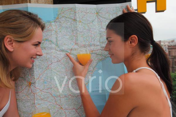 Two beautiful young women smiling, one woman holding glass of orange juice and pointing towards map