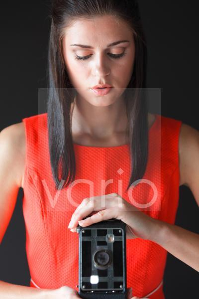 Beautiful young woman holding camera, looking down