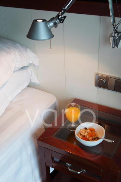 Orange juice with breakfast on table under illuminated lamp