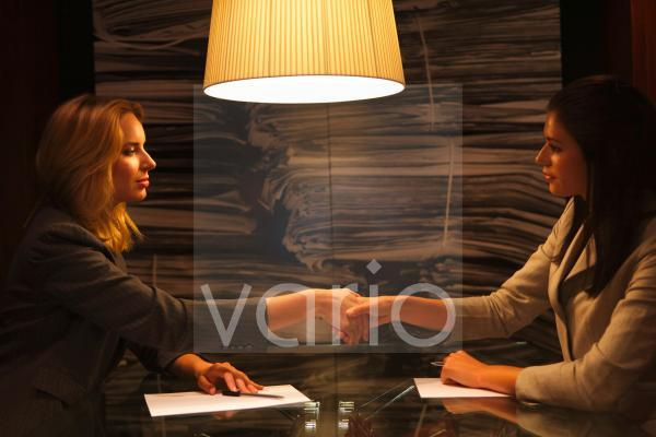 Two young business women shaking hands, sitting under illuminated lamp