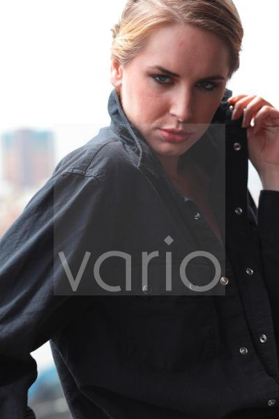 Close-up of a beautiful young woman holding collar of her jacket